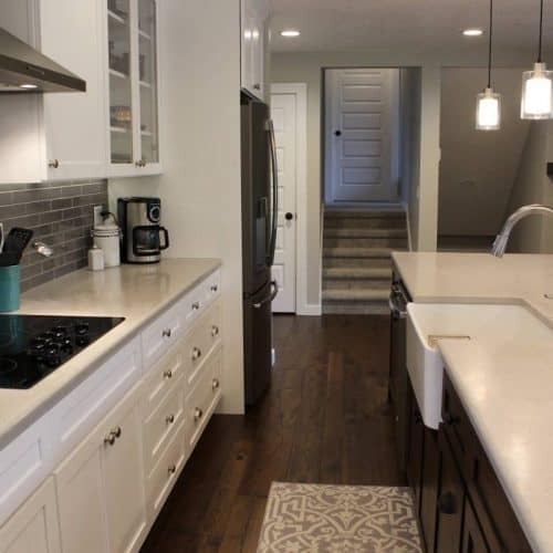 Crisp… clean… and open. Customer now has a 14 foot long center island for all of their entertaining needs! We sprayed all of the new cabinets in place with a white precatalized lacquer, and installed a knotty walnut center island with a farm style sink.